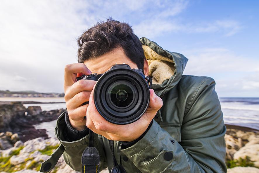A young man using a DSLR camera at the sea